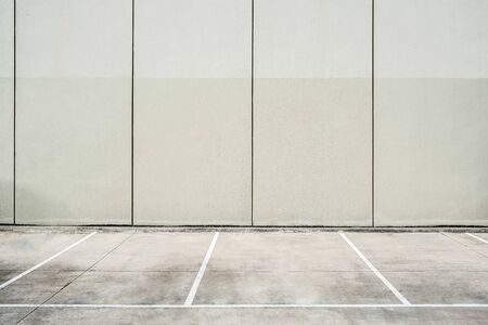 Empty parking lot next to concrete wall - clean geometric architecture shapes with copy space Stockfoto
