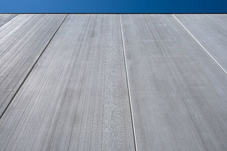 High concrete industrial building wall fragment with blue sky and copy space