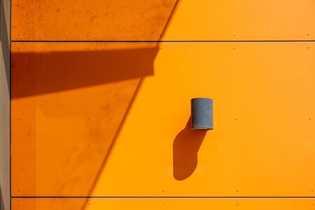 Exterior industrial wall mounted cylinder lamp on modern orange wall with strong shadows in bright daylight and copy space Stockfoto