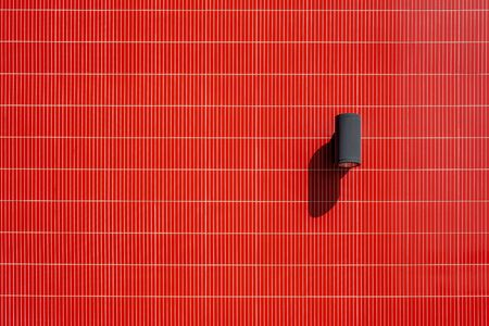 Industrial design outdoor spotlight lamp on vivid red tiled wall with copy space Stockfoto