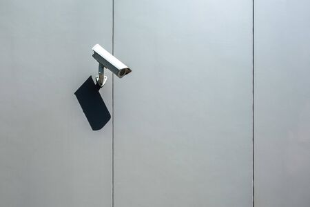 Security camera mounted on a wall of an industrial building with copy space