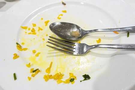 Empty white plate with rice food leftovers and cutlery after a meal closeup Stockfoto