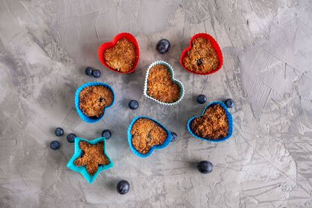 Healthy homemade cupcakes with blueberries on decorative concrete background - top view