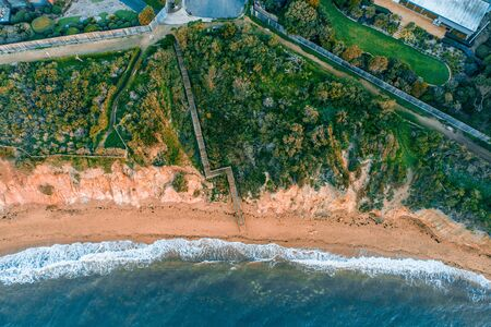 Looking down at long wooden stairs leading to a secluded ocean beach - aerial view