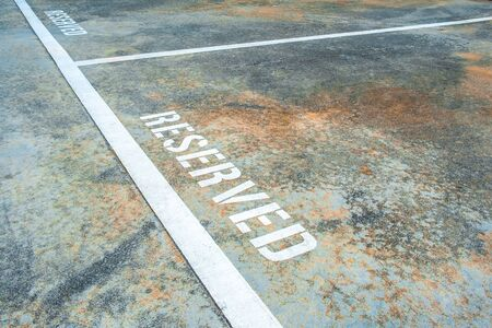 Closeup of reserved empty parking space on grungy old surface