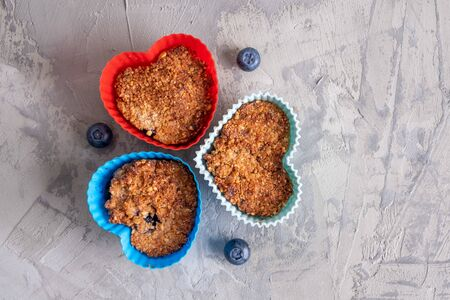 Homemade healthy cupcakes in heart shaped silicone moulds with blueberries  - top view