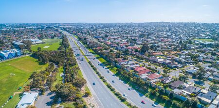 Cars driving on Monash freeway through Wheelers Hill suburb in Melbourne, Australia on sunny day - aerial panorama Stockfoto