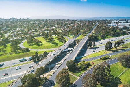 Highway interchange in bright sunlight with harsh shadows in Melbourne, Australia - aerial view