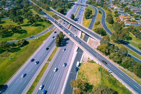 Looking down at cars driving on highway near interchange - aerial view