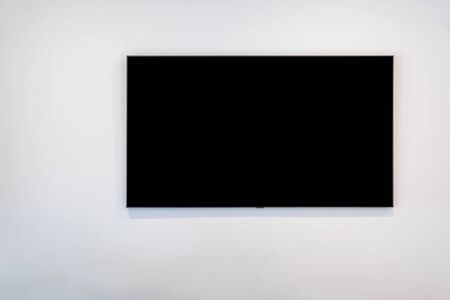 Black flat screen TV on white wall with copy space Stockfoto