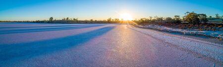 Wide panorama of pink salt lake Hardy at sunset