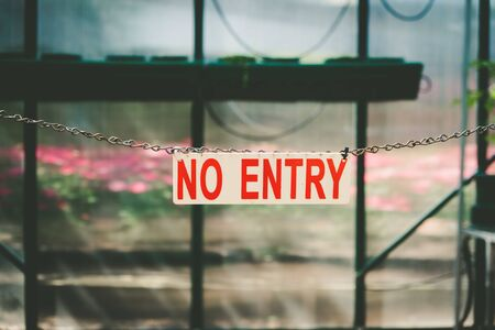 No Entry text sign hanging on a chain against blurred background