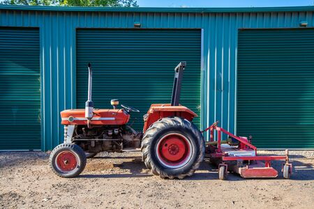 Old tractor with attached lawn mower against warehouse doors in Australia Stock Photo