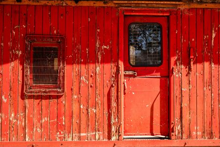 Old decaying train carriage with peeling red paint 写真素材