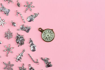 Arrangement of Christmas decorations with vintage decorative watch on pink background with copy space
