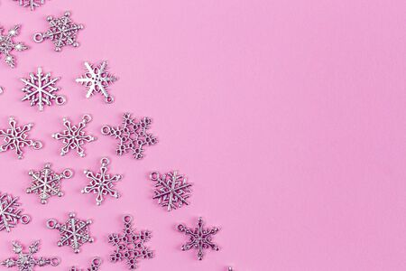 Silver snowflakes on pink background with copy space - holidays theme