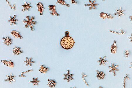 Christmas decorations arranged around vintage watch on light blue background - closeup with text space