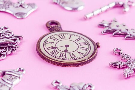 Closeup of vintage clock and Christmas decorations on pink background
