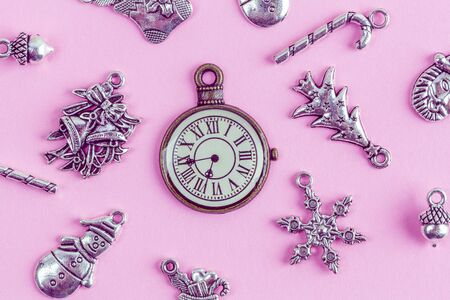 Christmas silver decorations with retro clock on pink background closeup