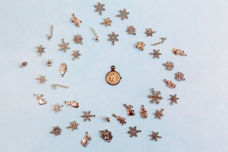 Christmas decorations arranged in circle around vintage decorative watch on light blue background - top view