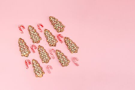 Christmas sweet food - trees biscuits with candy cantes on pink background. Top view with copy space