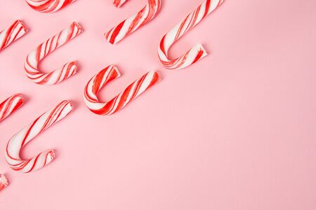 Candy canes pattern on pink background - top view with copy space