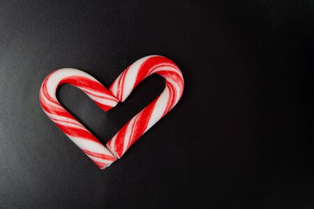 Candy canes arranged in heart shape on black background with copy space Фото со стока