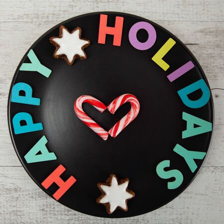 Happy Holidays colorful text on black plate with candy canes in heart shape - top view