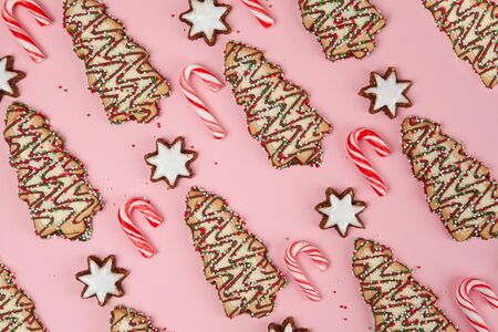 Christmas desserts background pattern - candy canes with stars and Christmas trees on pink, top view Фото со стока