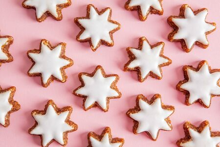 Hazelnut stars with icing pattern on pink background - top view