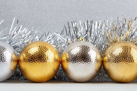 Row of Christmas baubles with silver tinsel on glittery background - closeup Фото со стока