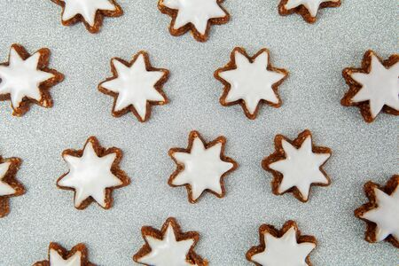 Almond stars with icing biscuits pattern on silver glitter background