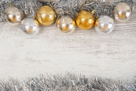 Baubles and tinsel on white rustic wood - top view with copy space
