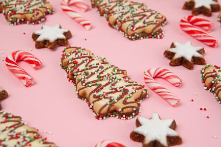 Christmas trees biscuits with candy canes and almond stars - pink background with shallow focus
