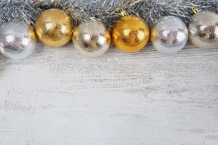 Golden and silver Christmas baubles on white rustic wooden background with copy space Фото со стока