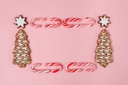 Christmas tree biscuits with almond stars and candy canes on pink background - top view with copy space