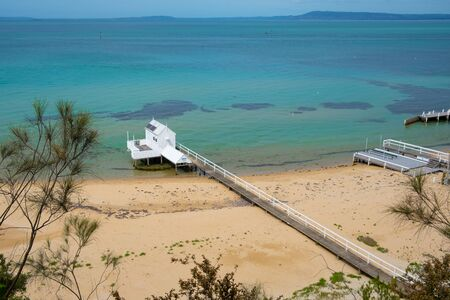 Long wooden pier extending over the beach into shallow turquoise bay water with white wooden shed at the tip