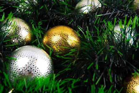 Shiny goldand silver Christmas baubles in green garland closeup with shallow focus Фото со стока