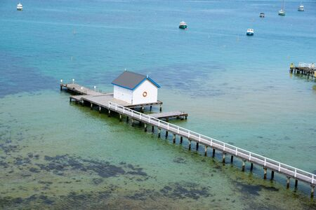 Long pier with white shed in turquoise shallow water and moored boats nearby