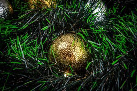 Beautiful shiny golden bauble among green tinsel - closeup