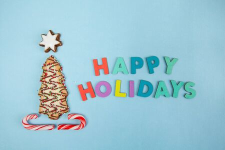 Christmas tree biscuit on blue background with Happy Holidays text - top view Фото со стока