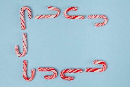 Candy canes arranged in a frame on blue background - top view with copy space Фото со стока