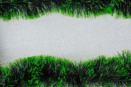 Green tinsel garlands on silver glittery background with copy space - Christmas and New Year theme