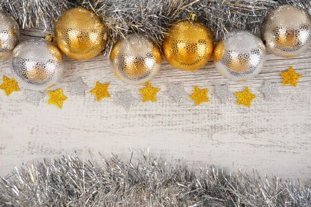 Gold and silver baubles and tinsel with glittery stars on white rustic wood - top view with copy space