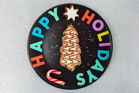 Christmas tree biscuit with happy holidays text on black plate and silver glitter background
