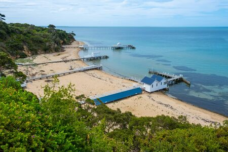 Several wooden piers with wooden cabins on shallow bay waters in Sorrento, Victoria, Australia
