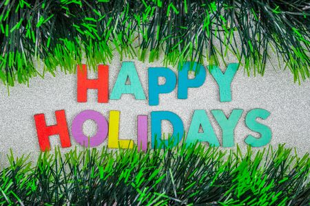 Happy Holidays text on glitter ornated with green tinsel garlands - top view