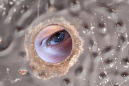 Serious blue eye looking through hole with copy space