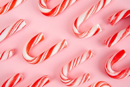 Christmas candy canes on pink background pattern Фото со стока