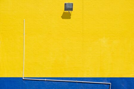 Large wall of building exterior painted in yellow and blue with pipe, flood light and copy space Фото со стока